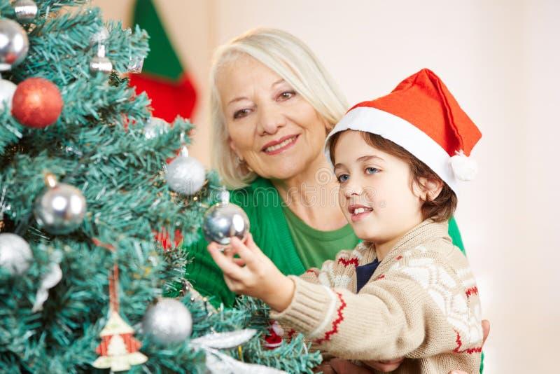 装饰圣诞树的孙帮助的祖母 免版税库存照片