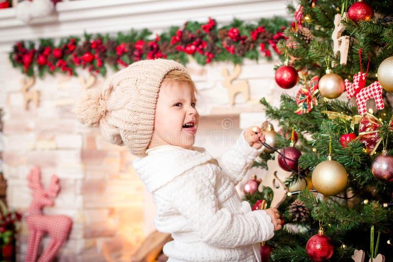 装饰圣诞树的小女孩在壁炉附近 免版税库存照片
