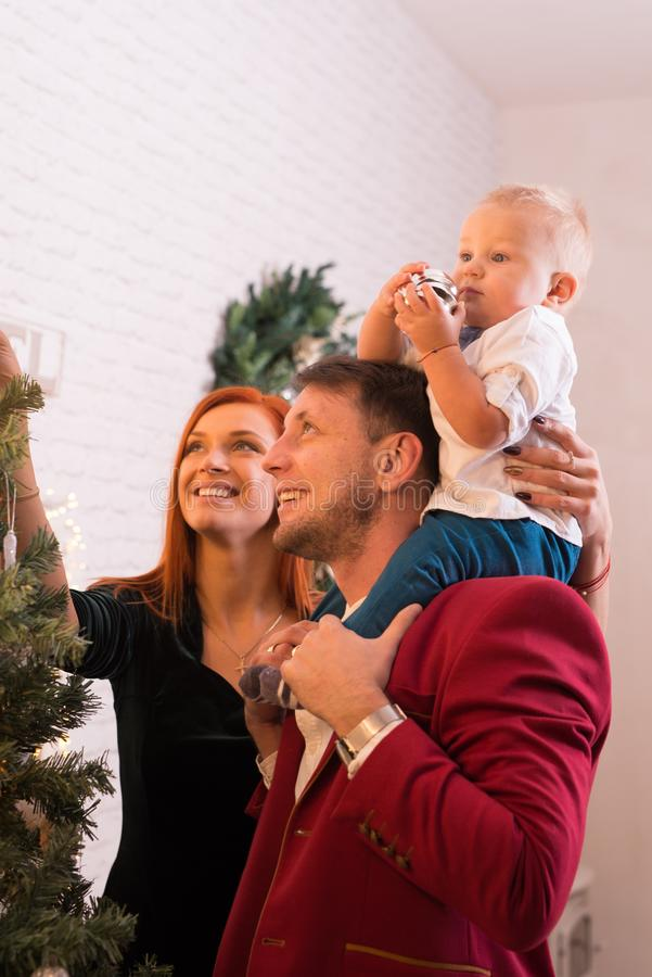 装饰圣诞树的年轻幸福家庭 免版税库存图片