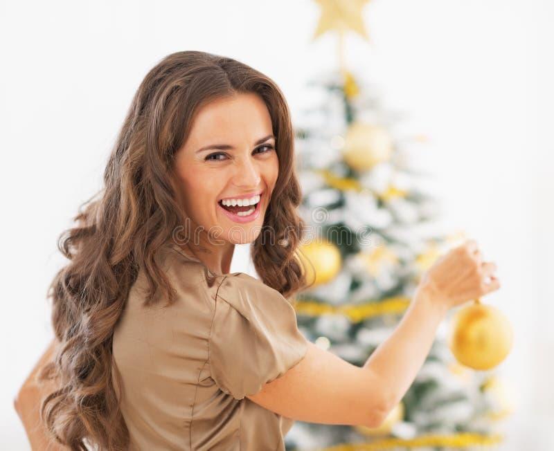 装饰圣诞树的微笑的少妇画象  免版税库存图片