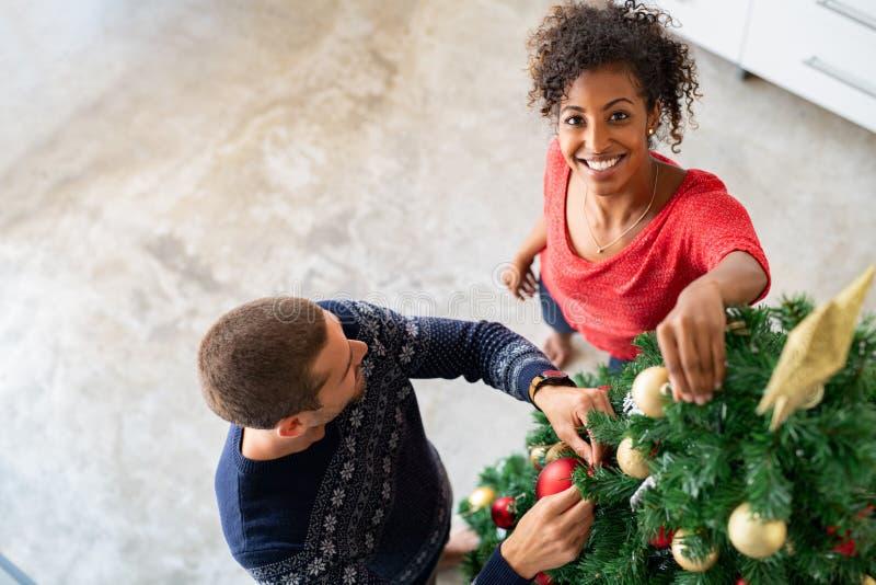 装饰圣诞树的愉快的夫妇 免版税库存照片