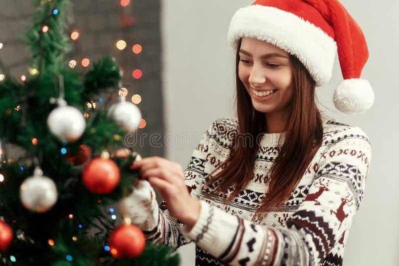 装饰圣诞树的愉快的妇女 佩带的毛线衣驯鹿 免版税库存照片
