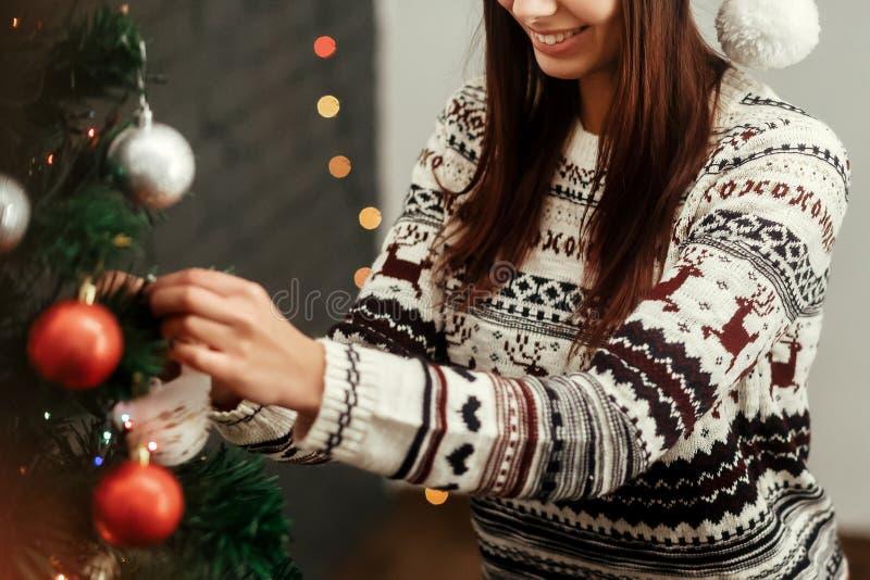 装饰圣诞树的时髦的愉快的妇女 佩带的毛线衣w 库存图片