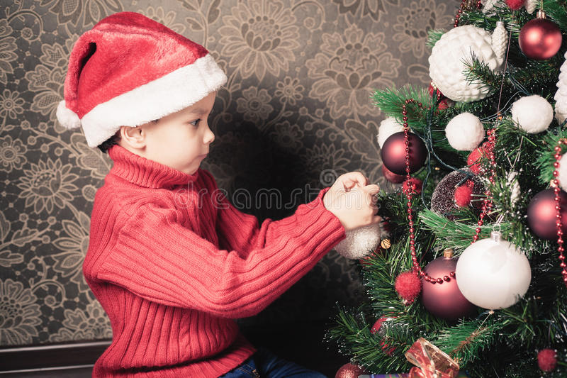 装饰圣诞树的男孩 免版税库存图片