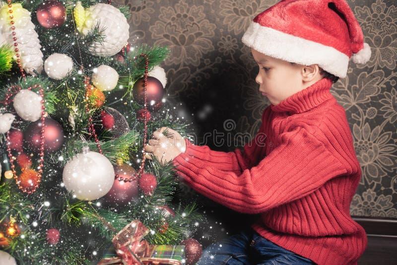 装饰圣诞树的男孩 库存图片