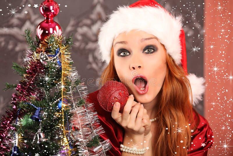 装饰圣诞树的美丽的妇女 免版税库存图片