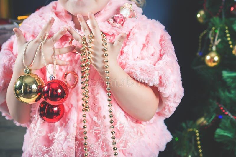 装饰圣诞树的滑稽的小女孩 免版税库存照片