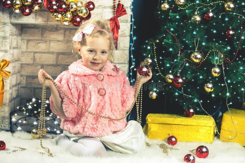 装饰圣诞树的滑稽的小女孩 免版税库存图片