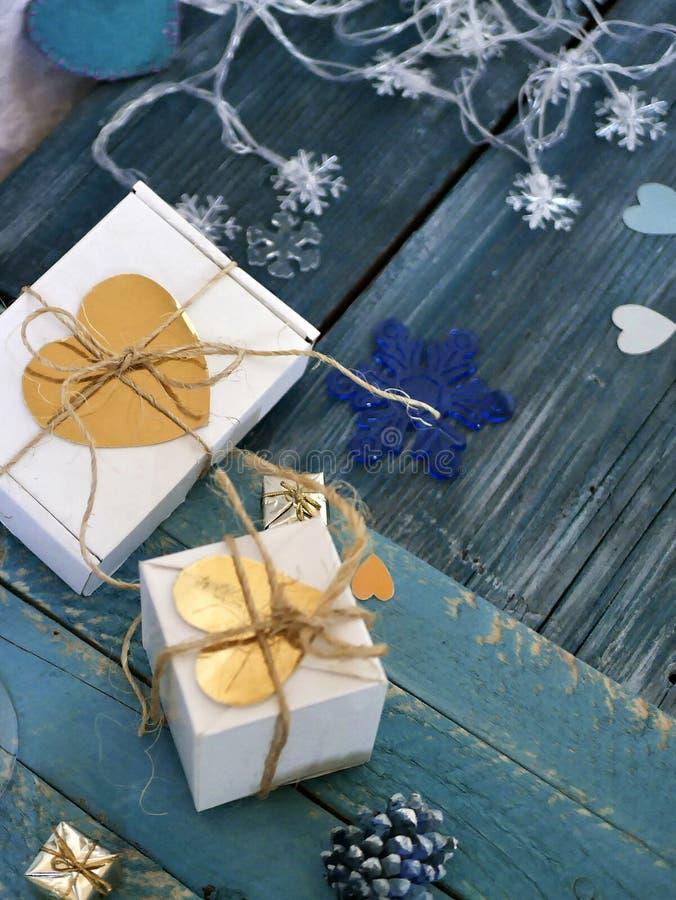 装饰圣诞节结构的装饰的礼物,圣诞灯,手工制造感觉心脏,在织地不很细木背景的纸 图库摄影
