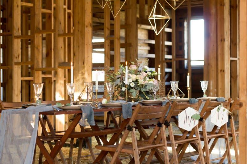 装饰在一个宴会前的婚礼桌在一个木谷仓 免版税库存照片