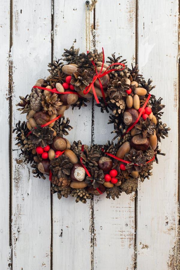 装饰在白色生锈的木板backround的圣诞节花圈,自然花圈,垂直 免版税图库摄影