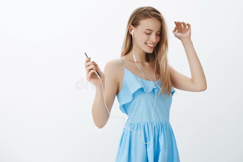 装饰在美丽的正式舞会礼服的女孩召回好的记忆作为与lisening音乐的耳机的跳舞,举行 免版税库存图片