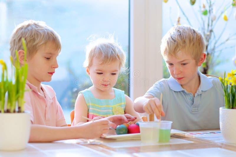 装饰复活节彩蛋的小组孩子 免版税库存照片