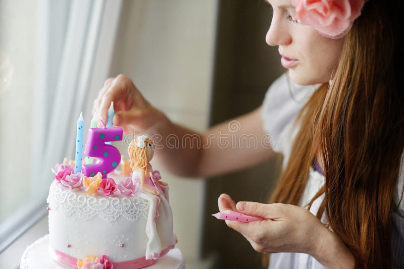 装饰女儿birhtday蛋糕的年轻母亲 免版税库存照片