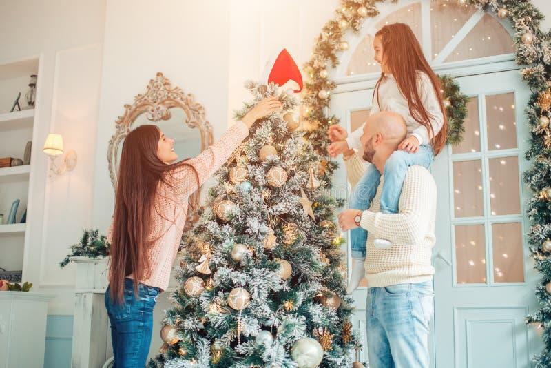 装饰女孩愉快的结构树的圣诞节 家庭,圣诞节,幸福概念 库存图片
