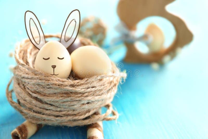 装饰巢用巧克力在颜色木桌上的复活节彩蛋 库存照片
