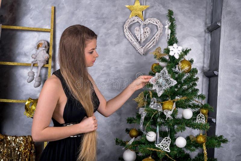 装饰庆祝的年轻白肤金发的妇女圣诞树 图库摄影