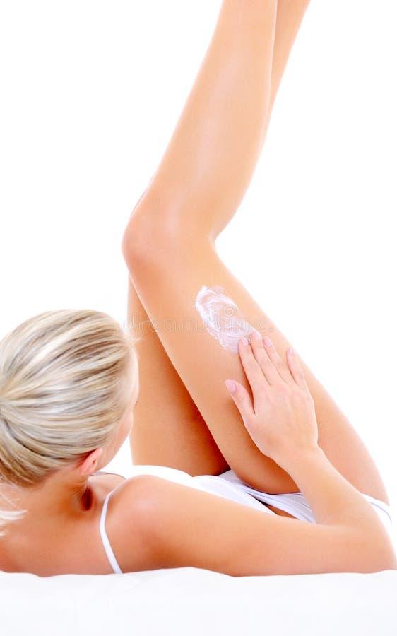 装饰性的奶油她的按摩妇女的臀部 库存照片