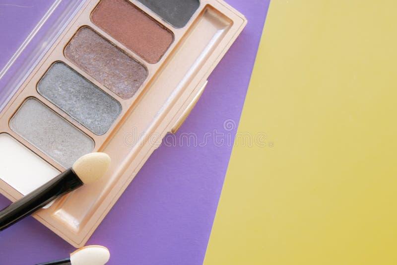 装饰性的辅助部件 刷子,在黄色的眼影膏,紫色背景 免版税库存照片