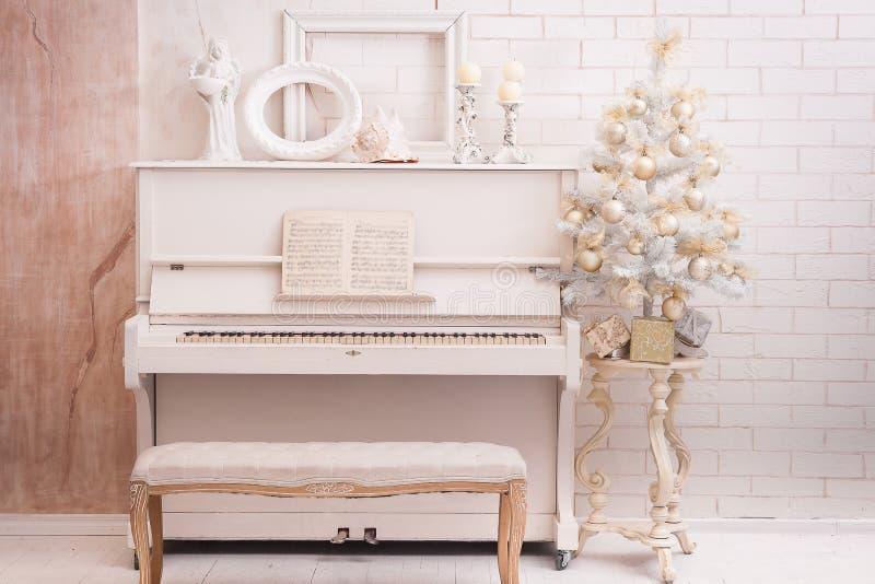 装饰新年度 在白色钢琴附近的圣诞树 免版税库存照片