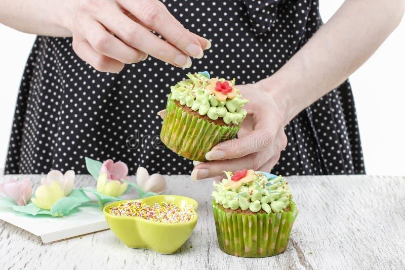 装饰杯形蛋糕的妇女 免版税库存图片
