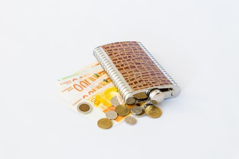 装饰用鳄鱼皮肤装饰酒精的一个烧瓶在堆说谎新的以色列sheke混杂的钞票和硬币  免版税库存图片