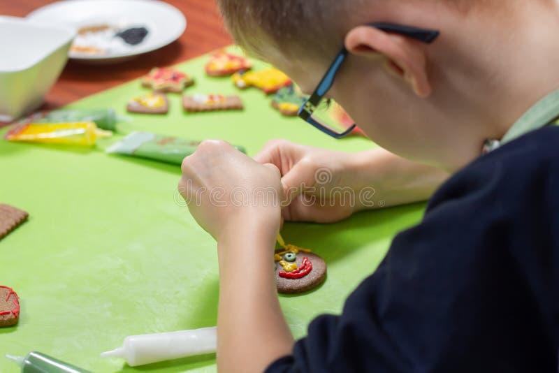 装饰由孩子的桂香曲奇饼 男孩的手形成色的结冰的面孔被紧压在管外面 无地址的饼干我 免版税库存照片