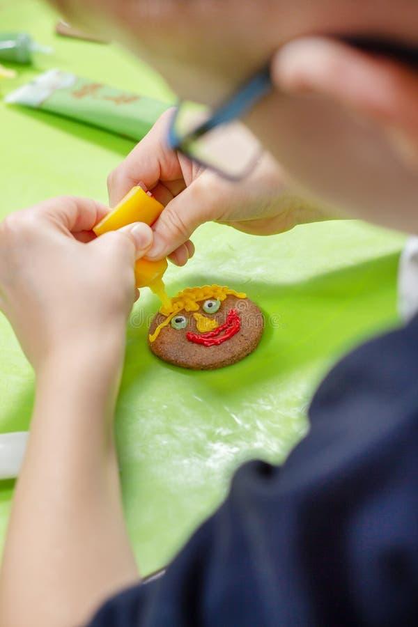 装饰由孩子的桂香曲奇饼 男孩的手形成色的结冰的面孔被紧压在管外面 无地址的饼干我 库存图片