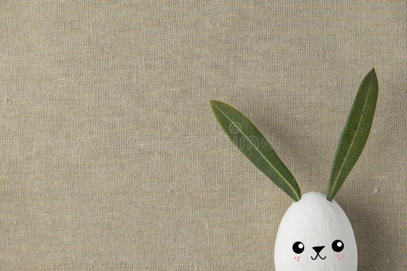 装饰白色与拉长的逗人喜爱的Kawaii微笑的面孔的被绘的复活节彩蛋兔宝宝 绿色留下耳朵 米黄亚麻制织品背景 库存照片