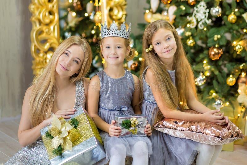 装饰白色绿色圣诞树的圣诞快乐和节日快乐逗人喜爱的小孩女孩户内用很多礼物 库存照片