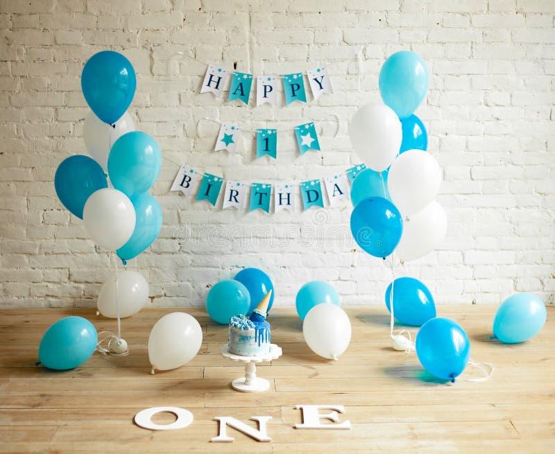 装饰的与气球、蛋糕和题字的一个年生日在墙壁和地板上 库存图片