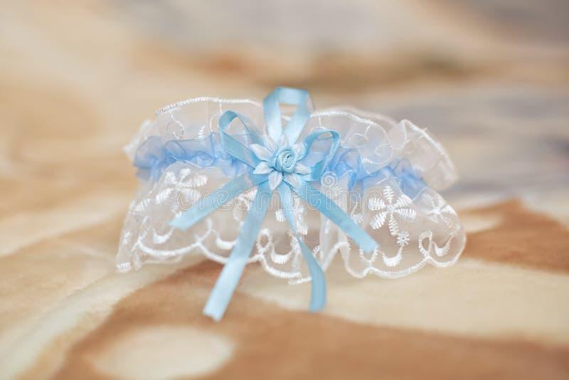 装饰的婚姻的袜带,米黄背景 婚姻概念 免版税库存照片