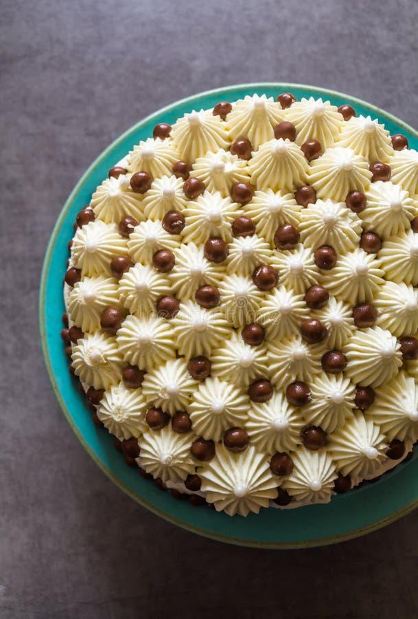 装饰的生日蛋糕顶视图与被鞭打的奶油和巧克力糖的在反对深灰背景的绿松石板材 库存照片