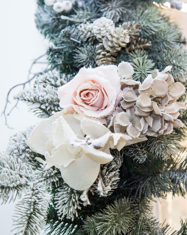 装饰的美好的白花和圣诞树分支,与装饰的明亮的内部在背景 库存图片