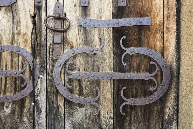 装饰的铁板条和门把手在中世纪木门 免版税库存图片
