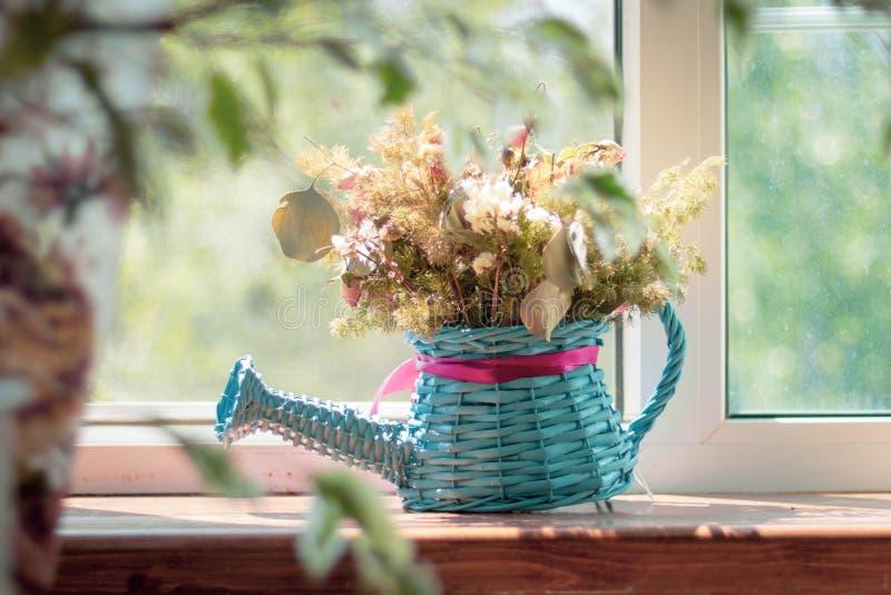 装饰花瓶-与一把桃红色弓的一把蓝色柳条喷壶与干燥野花干燥标本集,在国家的窗台站立 库存图片