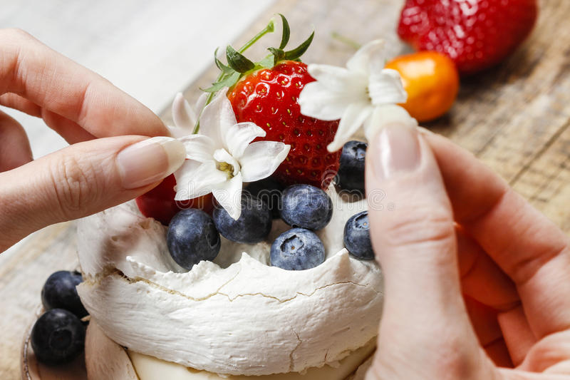装饰蛋白甜饼蛋糕的妇女 库存图片