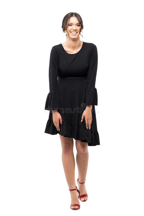 黑装饰衣裙礼服的自发笑的年轻拉丁妇女 库存图片
