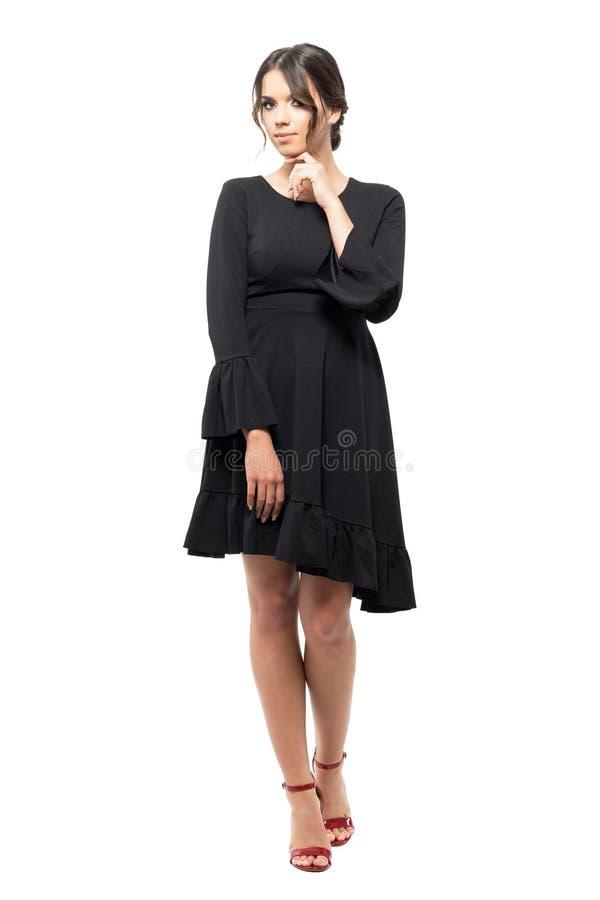 黑装饰衣裙礼服的诱人的年轻拉丁妇女用在下巴的手 免版税库存照片