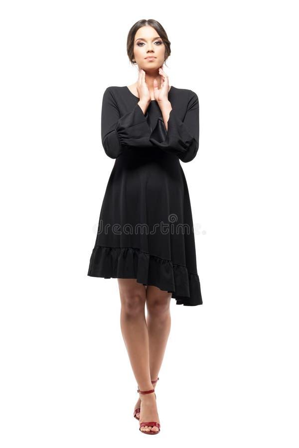 装饰衣裙黑色礼服的华美的诱人的拉丁妇女用接触她的面孔的手 免版税库存照片
