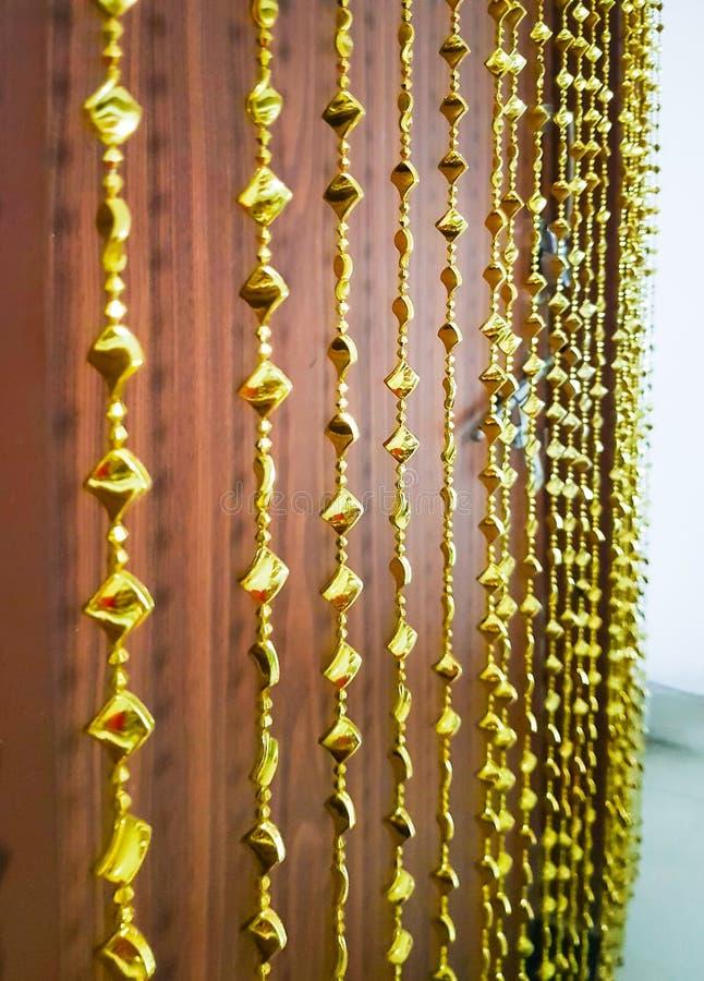 装饰门帘暂停的和浅dept的金黄编钟 免版税库存图片