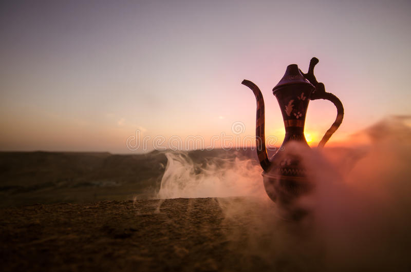 装饰阿拉伯花瓶和水罐被生动描述在日落 图库摄影