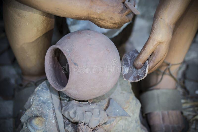 装饰黏土碗的史前人与原物一样大小雕塑 库存图片
