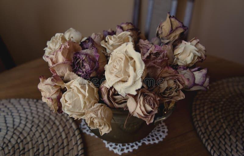 装饰:在一个减速火箭的花瓶的干玫瑰 图库摄影