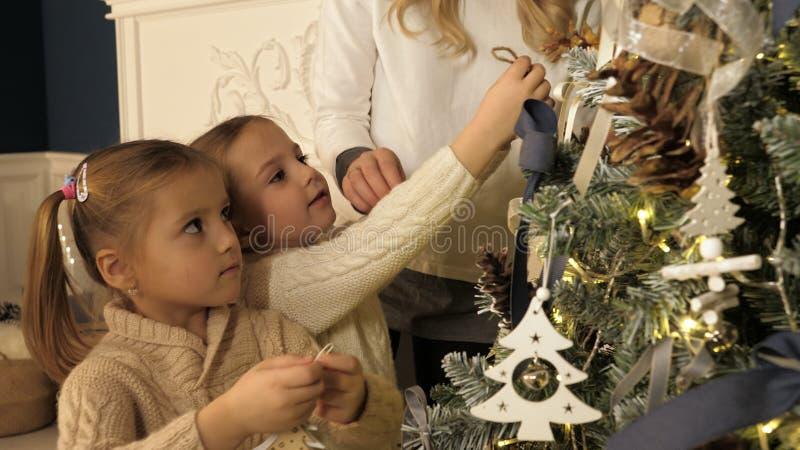 装饰Xmas树的母亲和孩子在有壁炉的美丽的家庭客厅 免版税图库摄影