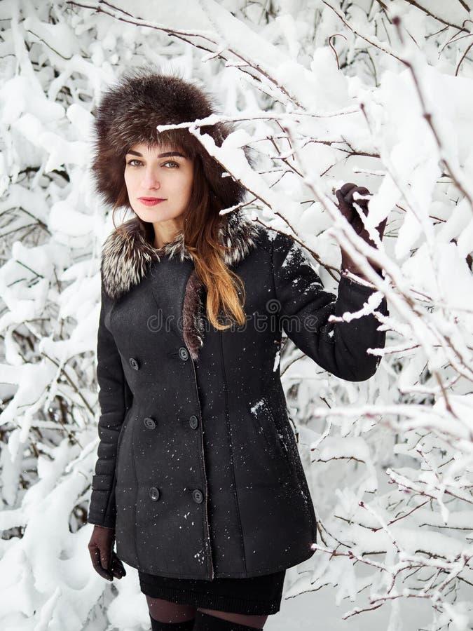 裘皮帽的可爱的愉快的年轻深色的妇女有乐趣多雪的冬天公园森林本质上 免版税库存照片