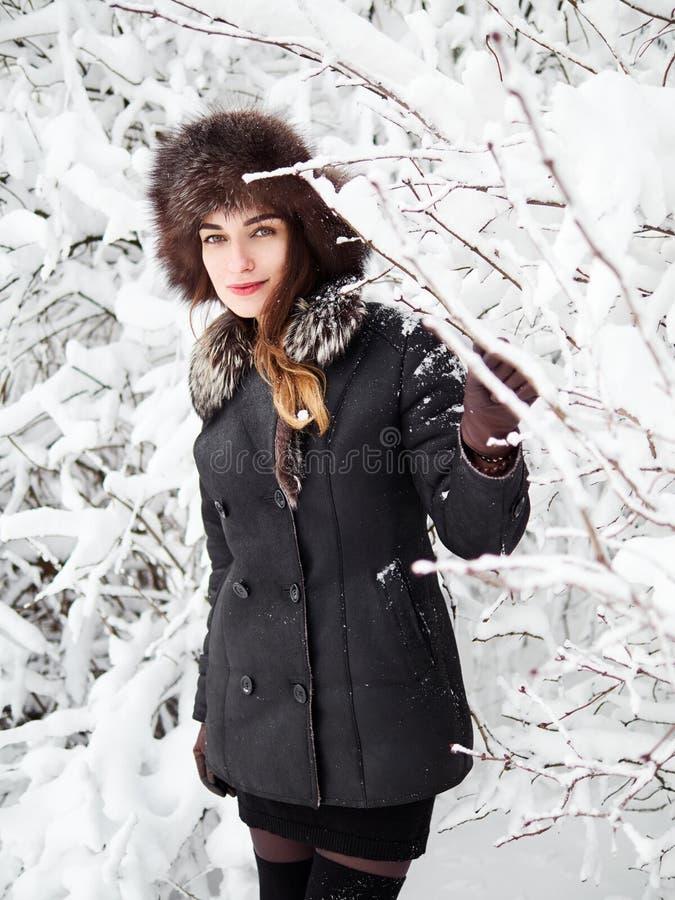 裘皮帽的可爱的愉快的年轻深色的妇女有乐趣多雪的冬天公园森林本质上 库存图片
