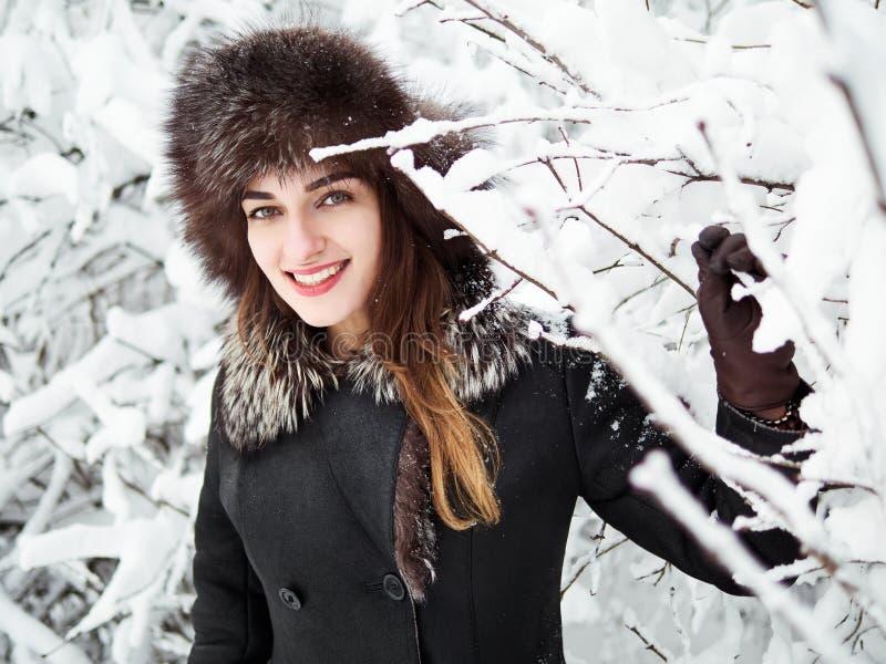 裘皮帽的可爱的愉快的年轻深色的妇女有乐趣多雪的冬天公园森林本质上 库存照片