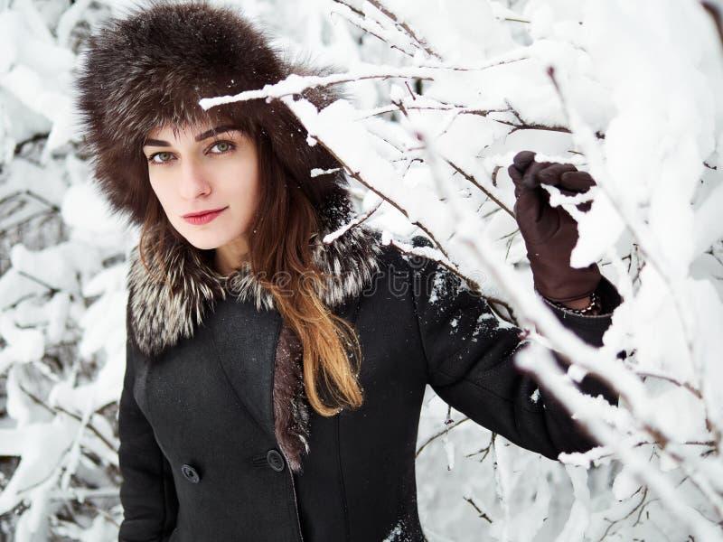 裘皮帽的可爱的愉快的年轻深色的妇女有乐趣多雪的冬天公园森林本质上 图库摄影
