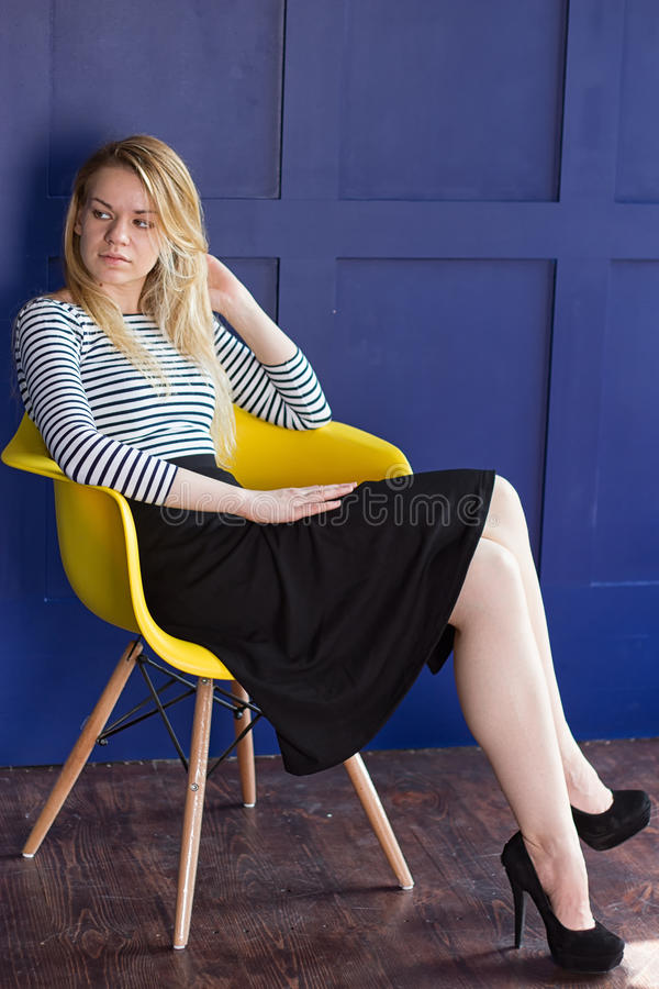 裙子和背心的白肤金发的女孩坐椅子 免版税库存照片